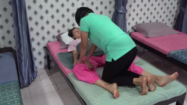 Thai massage. A woman is lying on the bed. The masseuse massages the womans thigh.
