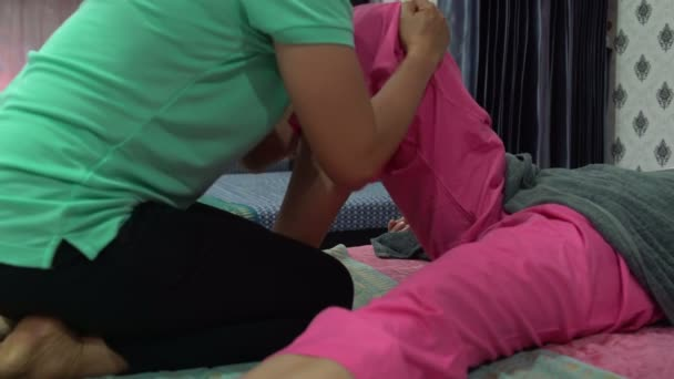 Thai massage. The masseuse massages the womans thigh. A woman is lying on the bed.