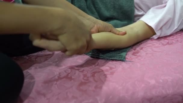 Thai massage. A woman is lying on the bed. The masseuse massages a womans hand.