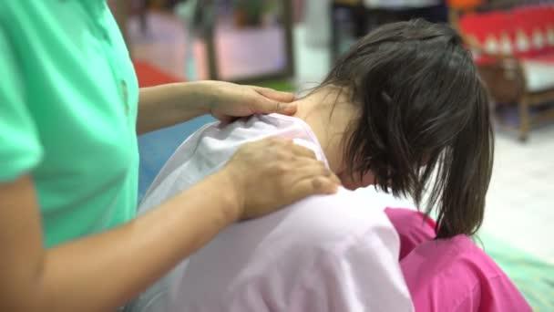 Thai massage. The masseuse massages the womans neck.