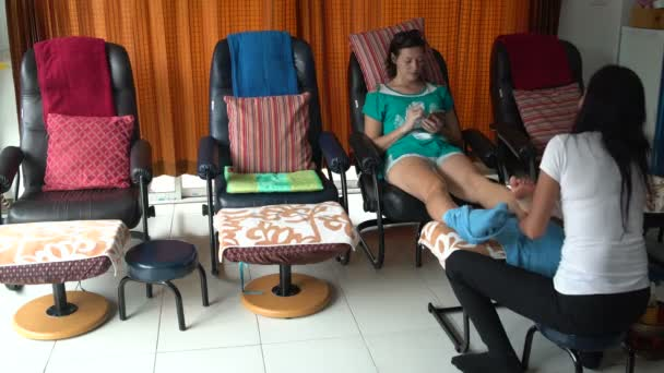 A woman is sitting in a chair with a smartphone. Masseuse massages a womans leg using oil