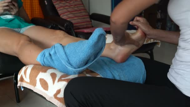 Masseuse massages a womans leg using oil. Thai foot massage.