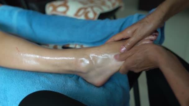 Massaggio tailandese dei piedi. La massaggiatrice massaggi un piede womans