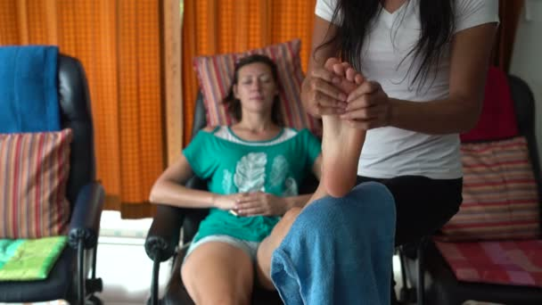 Thajská masáž. Masérka masíruje Zenske nohy. Žena odpočívá, sedí v křesle.