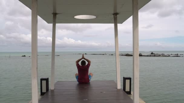 Man is engaged in meditation by the sea