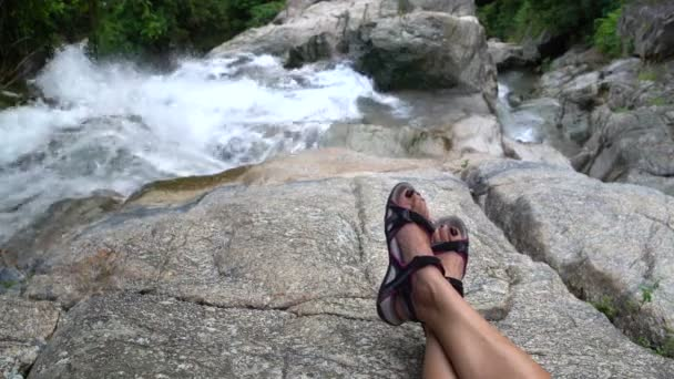Womens feet against the backdrop of a waterfall