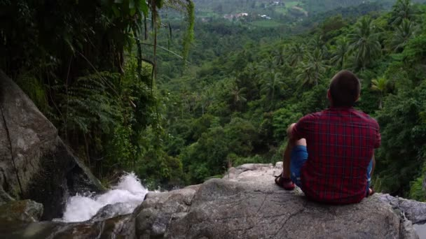 A man sits on a rock beside a waterfall