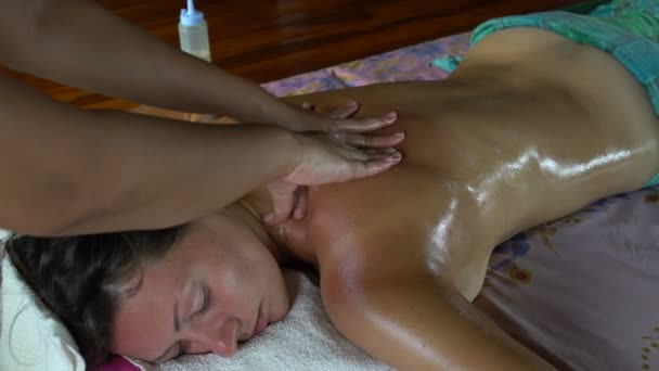 Thai massage with oil. Masseuse massages womans back