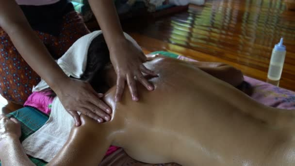 The masseuse massages the womans back. Thai massage with oil