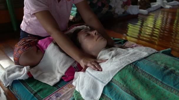 Masáž Thajská rameno. Masérka masíruje ramena Zenske přes ručník