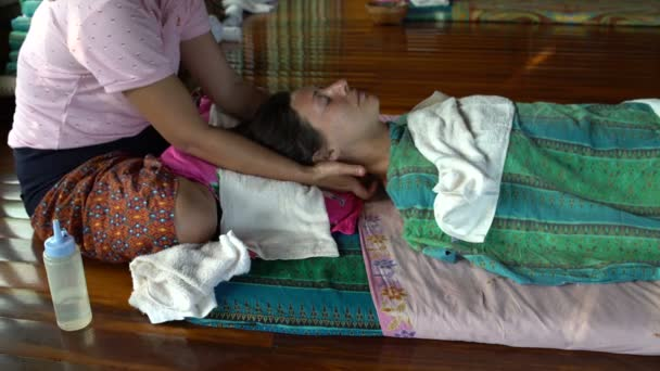 Thai head massage. The masseuse massages the neck and temporal area of a woman