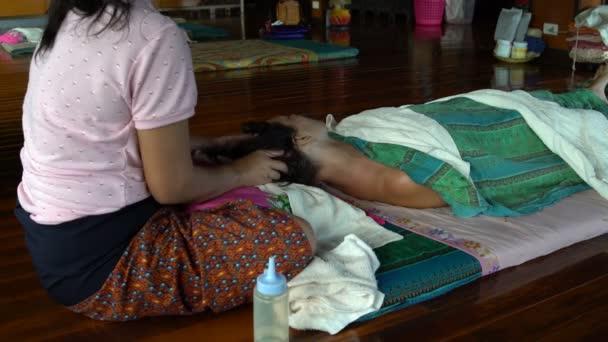 Thajská masáž hlavy. Masérka masíruje ženách vlasy