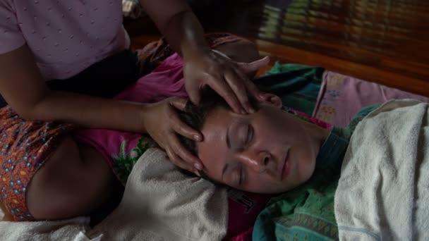 Thai Kopfmassage. Die Masseurin massiert die Schläfenregion und Womans Gesicht