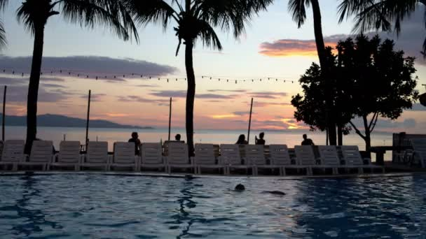 A man is resting in the pool on the sunset background