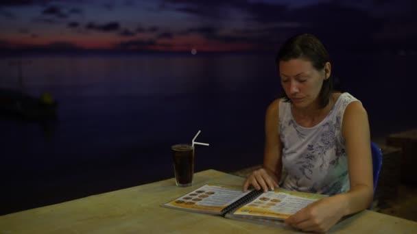 Žena sedí v kavárně u stolu na západ slunce na pozadí pohledu na menu a pití koktejlů