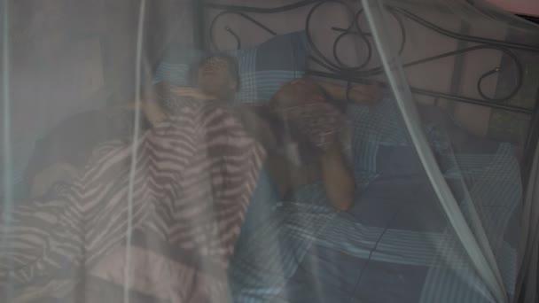 Muž objímání ženu v posteli s nebesy