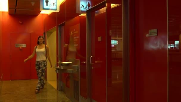 Eine Frau kommt aus der öffentlichen Toilette