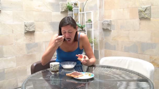 Žena je jíst müsli a toasty s marmeládou