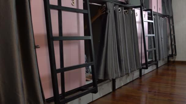 Una donna emerge da una cella in un capsule hotel