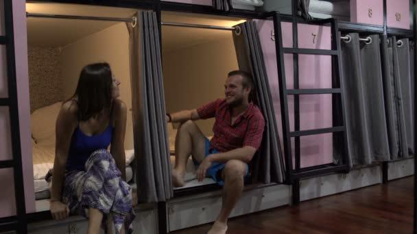 La capsula hotel, un uomo e una donna sedersi sul bordo dei letti e parliamo