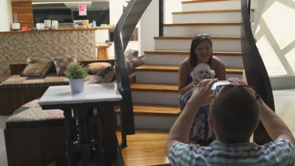 A man takes pictures of a woman sitting on the stairs in the house with a small dog in her arms