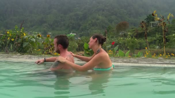 A woman massages a mans back in a pool with thermal water