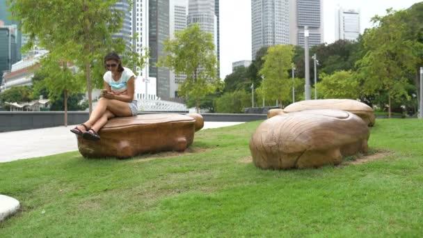 Žena sedí na kamennou lavičku v podobě želvy a používá smartphone
