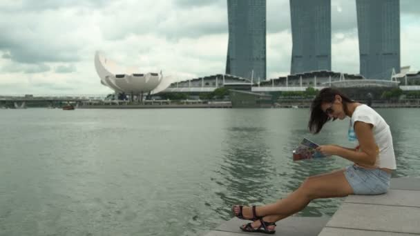 A woman sits with a map on embankment of the Marina Bay in Singapore overlooking the hotel
