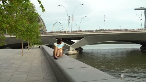 Žena sedí na zábradlí na nábřeží řeky