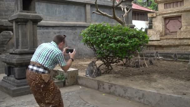 Egy ember veszi a képek a majmok egy okostelefon