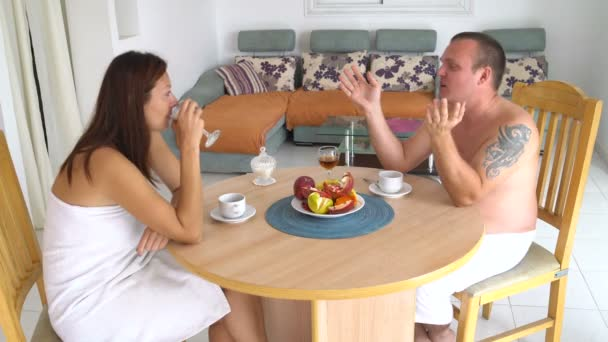 A man and a woman are sitting at a table at home in the living room drinking red wine and talking.