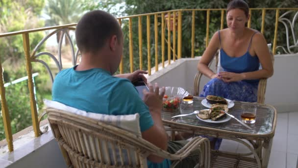 Woman and man eat sitting at the table on the balcony. Man taking a picture on smartphone