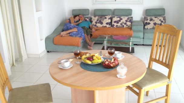 Man and woman lie on the couch and eat fruit