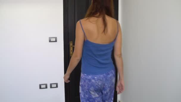 Frau schaltet Licht aus und verlässt den Raum