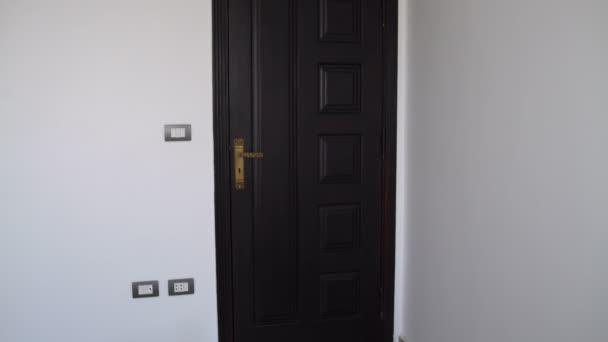 eine Frau öffnet die Tür schaltet das Licht ein und betritt den Raum