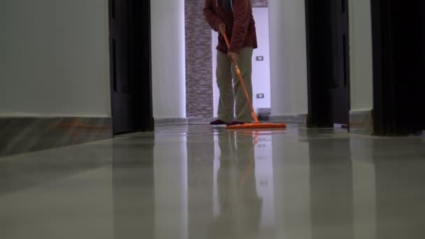 Muž omývá podlah mopem v chodbě