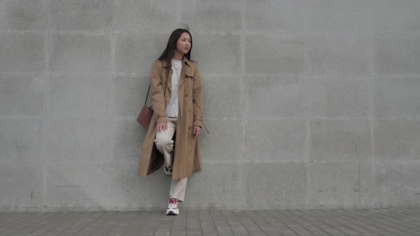 Dívka módně oblečená stojí opřená o betonovou zeď