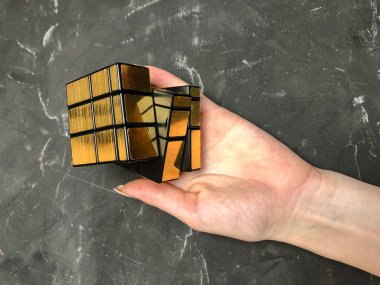 Rubik's cube 3x3 in men's hands, close-up, top view, marble background.