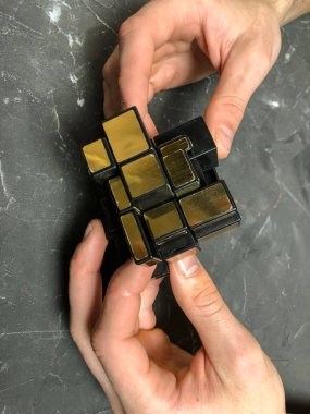 men's hands holding a magic mirror cube on a marble background. with copy space.