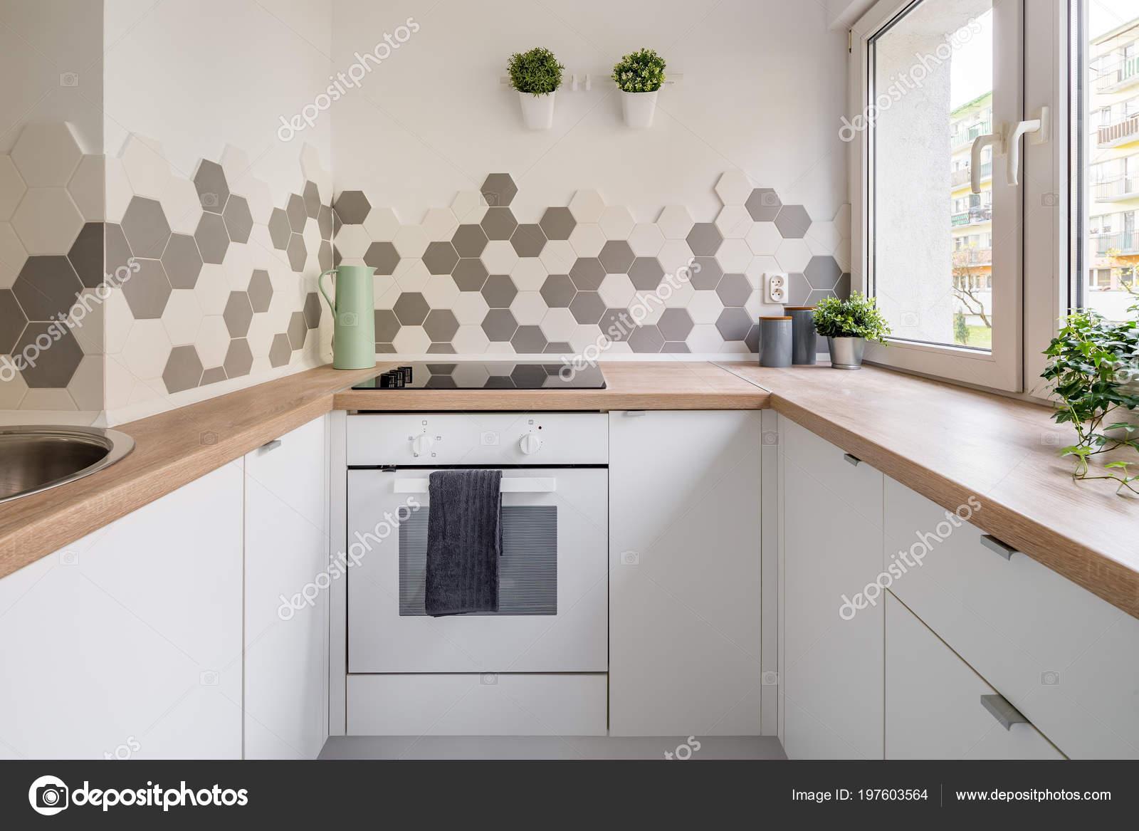 Cucina stile scandinavo con armadi bianchi controsoffitto legno