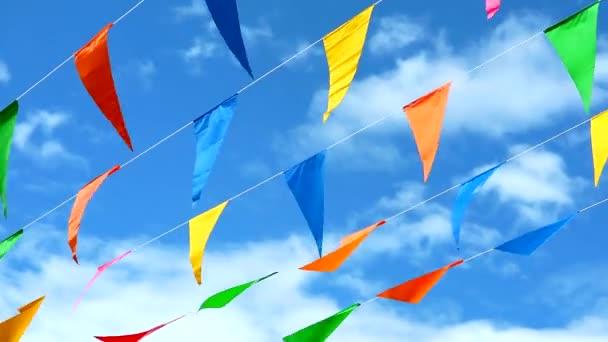 színes háromszög alakú zászló mozog a szél a kék ég fehér felhő