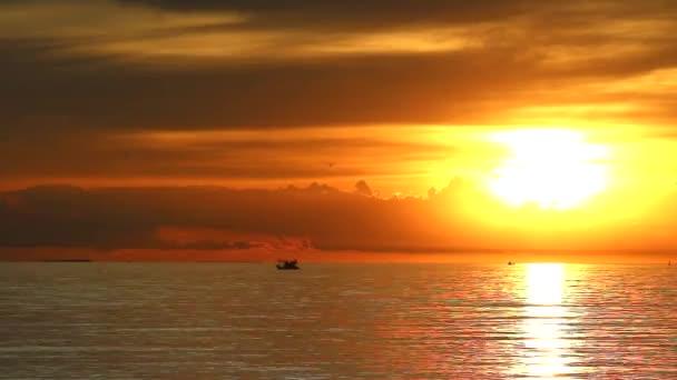 Západ slunce na moři silueta mraku rybářská loď doba stěhování se propadá
