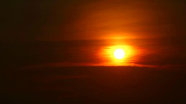 Rudý plamen slunce na oranžovém nebi a temně rudý mrak na moři