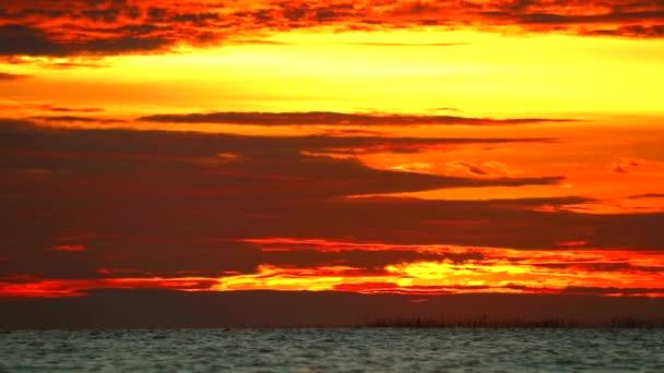 Rudý plamen slunce na oranžovém nebi a temně rudý mrak na moři a létání se vrací domů