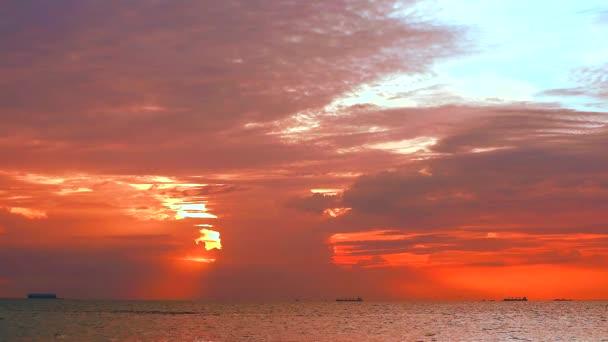 světlo slunce na obloze a temně rudé mraky na moři a nákladní lodi parkování