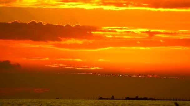 červený plamen východu slunce na oranžové obloze a temně rudý mrak na moři