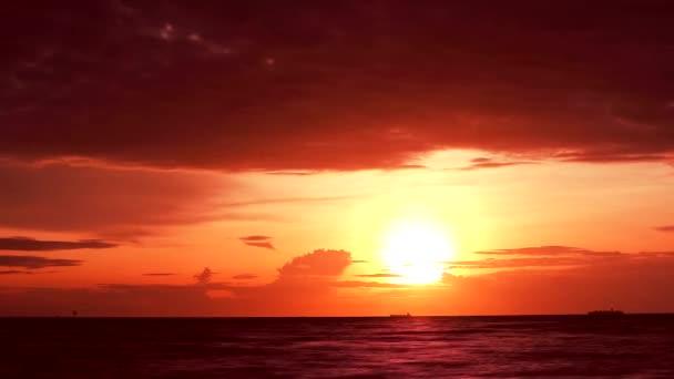 Rudá oranžová obloha a temně rudý mrak pohybující se na moři