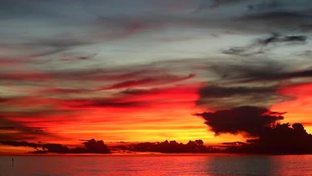 barevný plamen západ slunce na oranžové obloze a tmavě červený mrak na moři