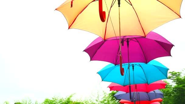bunte Schirmlinie schmücken Outdoor-Bewegung durch Wind auf blauem Himmel weiße Wolke