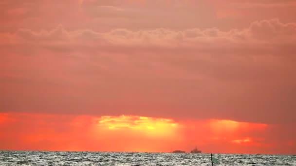 rozmazané oranžové nebe a červený mrak pohybující se a vlna na moři